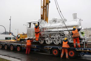 Workers using crane to unload locomotive